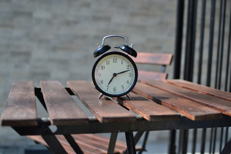 An old fashioned alarm clock on a table.